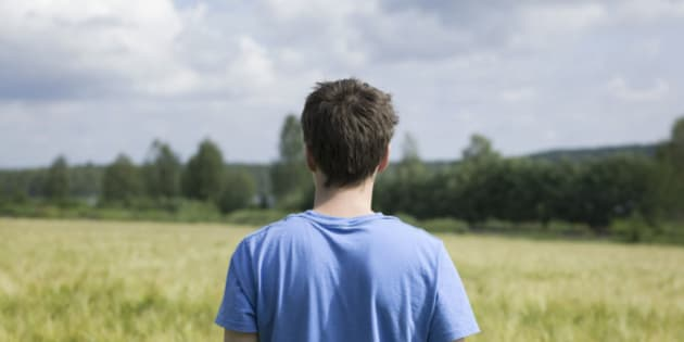 Rear view of a young man standing in a field