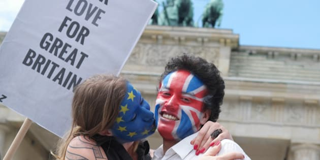 "A young couple  with  faces paint in European, left,  and British  colors, pose with a sign ""Our Love For Great Britain"" during a Kiss Marathon event   at Brandenburg Gate in Berlin, Germany, Sunday June 19,  2016 to support the ' Remain'  voters in Britain's referendum. The campaign in the referendum over Britain's future in the European Union is about to resume full throttle after being on hold due to the killing of a popular lawmaker.  British voters head to the polls on Thursday to decide if the country should stay in the European Union or leave it.  (Joerg Carstensen/dpa via AP)"