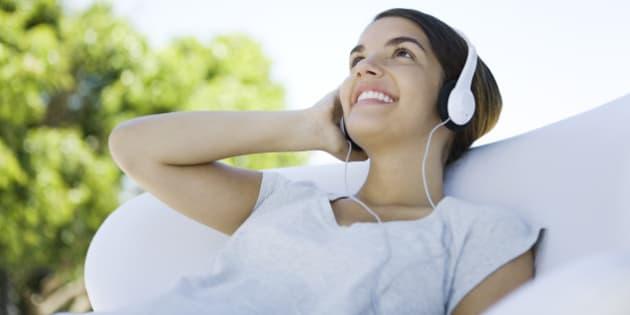 Teenage girl listening to headphones, looking up, smiling