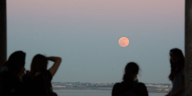 A group of girls watches a full Strawberry Moon, or Rose Moon, rise above the Tagus river in Lisbon Tuesday, June 2, 2015. Strawberry Moon was the name given by native American Algonquin tribes to the June full moon while in Europe it's often called Rose Moon. (AP Photo/Armando Franca)