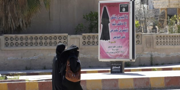 "Veiled women walk past a billboard that carries a verse from Koran urging women to wear a hijab in the northern province of Raqqa March 31, 2014. The Islamic State in Iraq and the Levant (ISIL) has imposed sweeping restrictions on personal freedoms in the northern province of Raqqa. Among the restrictions, Women must wear the niqab, or full face veil, in public or face unspecified punishments ""in accordance with sharia"", or Islamic law. REUTERS/Stringer   (SYRIA - Tags: POLITICS CIVIL UNREST CONFLICT RELIGION SOCIETY)"