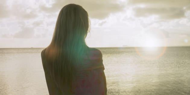Woman on the beach watching the horizon