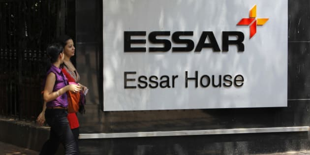 Employees walk past an Essar Group logo outside their headquarters in Mumbai May 20, 2013. India's Economic Times newspaper said the Essar Group conglomerate would sign a financial agreement with China's China Development Bank and China's largest oil and gas producer PetroChina Company during Chinese Premier Li Keqiang's trip to India. REUTERS/Vivek Prakash (INDIA - Tags: BUSINESS LOGO ENERGY POLITICS)