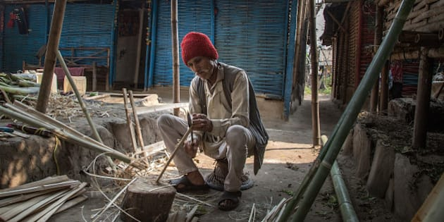 BELDANGI, NEPAL - MARCH 14:  Dal Bahadur Bista, 70 years old, cuts bamboos to make furniture in front of his house in the Beldangi 2 refugee camp on March 14, 2015 in Beldangi, Nepal. Dal arrived 23 years ago after escaping from Bhutan where he was jailed for more than one year after being accused of not paying government taxes. Dal used to work as a tax revenue collector in Bhutan. More than 22,000 Bhutanese refugees still reside in the refugee camps set up in Nepal in the 1990s, after hundreds of thousands of Bhutanese fled the country following a campaign of ethnic cleansing by the Bhutanese Government against the country's ethnic Nepali population. After more than 20 years in Nepal, over 90% of the refugees have been successfully resettled in third countries, thanks to programs by UNHCR and IOM. Those remaining the camps are supported by several organizations that undertake a wide variety of projects. Helped by remittances sent back to Nepal by families already resettled in other countries, the refugees still in the camps have set up their own small businesses in the camps and the roads near them, roads which are also replete with Nepali-owned businesses who benefit directly from the refugees that are still waiting in Nepal to be resettled in third countries. (Photo by Omar Havana/Getty Images)