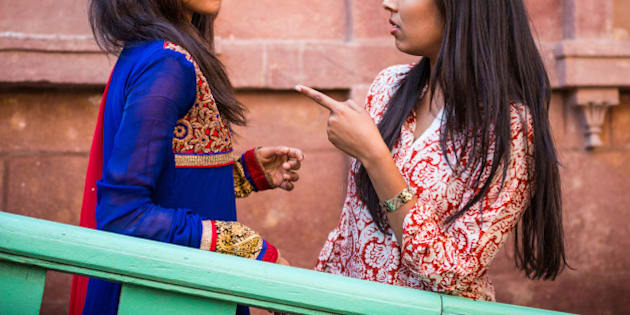 Two young Indian having an argument. One is pointing her index finger at the other to warn her.
