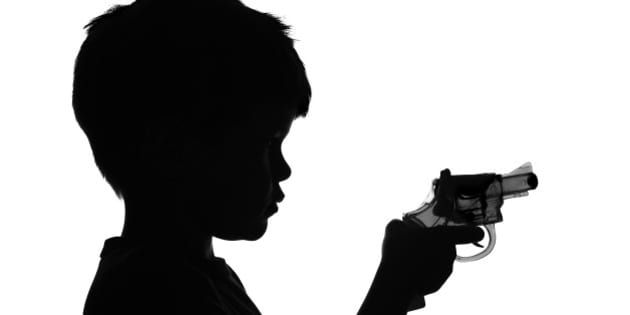 B&W Silhouette of a boy holding a toy gun