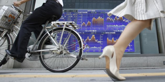 People pass by an electronic board displaying graphs of Japanese stock indices outside a brokerage in Tokyo August 17, 2010. Japan's Nikkei share average fell 0.4 percent to its lowest close in more than eight months on Tuesday, with the yen holding onto gains against the dollar as mounting signs of weak economic growth dampened appetite for risk.   REUTERS/Yuriko Nakao (JAPAN - Tags: BUSINESS EMPLOYMENT)