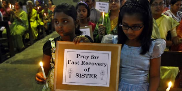 "Girls hold a placard and candles during a special prayer service at a church to show solidarity with the nun who was raped during an armed assault on a convent school, in Kolkata March 17, 2015. Indian Prime Minister Narendra Modi said on Tuesday he was ""deeply concerned"" about the rape of an elderly nun and the demolition of a church as protests for the better protection of women and religious minorities erupted across the country. REUTERS/Rupak De Chowdhuri (INDIA - Tags: CRIME LAW RELIGION POLITICS)"