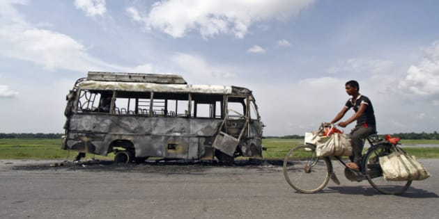 A man rides a bicycle in front of a bus that was burnt by a mob on the national highway near Rongia town in the northeastern Indian state of Assam August 16, 2012. Fresh violence flared in previously calm areas of Assam on Thursday, with a hundreds-strong mob burning a bus and a wooden bridge in apparent retaliation for a similar attack on a car, officials said. REUTERS/Utpal Baruah (INDIA - Tags: CIVIL UNREST POLITICS TPX IMAGES OF THE DAY)