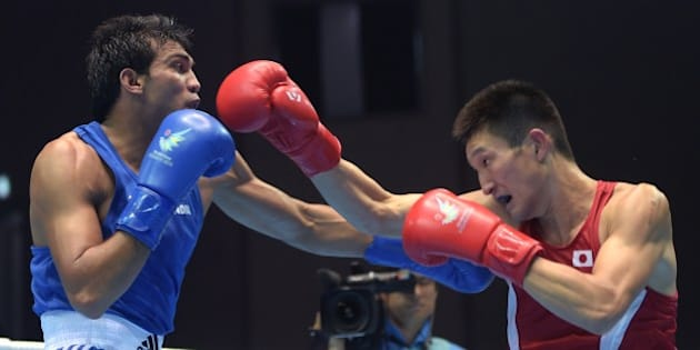 Japan's Masatsugu Kawachi (R) competes against India's Kumar Manoj (L) in the men's bosing light welter 64 kg preliminaries session 4 during the 2014 Asian Games in Incheon on September 25, 2014. AFP PHOTO / PORNCHAI KITTIWONGSAKUL        (Photo credit should read PORNCHAI KITTIWONGSAKUL/AFP/Getty Images)