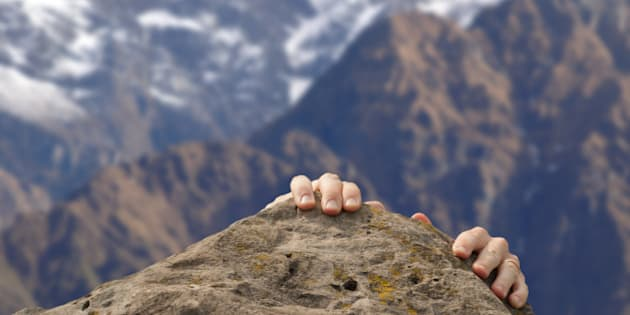Hands grasp a summit in front of the Himalayas