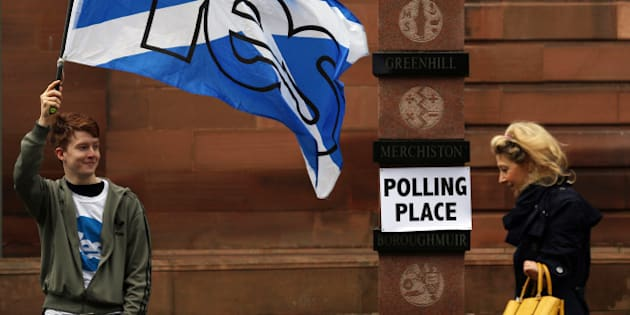 A voter in Scotland's Independence Referendum, right, walks past a YES supporter as she  arrives at a polling place in Edinburgh,Thursday, Sept. 18, 2014. Polls opened across Scotland in a referendum that will decide whether the country leaves its 307-year-old union with England and becomes an independent state.(AP Photo/David Cheskin)