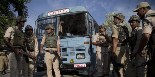 Indian security personnel stand guard near the bus that was carrying paramilitary soldiers damaged after a highway ambush by suspected rebels in Pampore, on the outskirts of Srinagar, Indian controlled Kashmir, Saturday, June 25, 2016. Some paramilitary soldiers were killed and about 20 were wounded in the incident. (AP Photo/Dar Yasin)