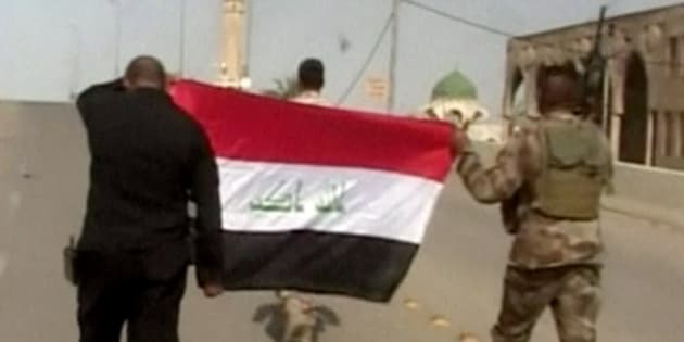 """This image made from Associated Press video shows, Iraqi soldiers carrying an Iraqi flag to hoist on buildings after a senior Iraqi commander declared that the city of Fallujah was """"fully liberated"""" from Islamic State group militants, in Fallujah, Iraq, Sunday, June 26, 2016. (AP Video via AP)"""