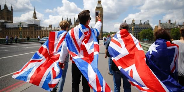 People walk over Westminster Bridge wrapped in Union flags, towards the Queen Elizabeth Tower (Big Ben) and The Houses of Parliament in central London on June 26, 2016.  Britain's opposition Labour party plunged into turmoil Sunday and the prospect of Scottish independence drew closer, ahead of a showdown with EU leaders over the country's seismic vote to leave the bloc. Two days after Prime Minister David Cameron resigned over his failure to keep Britain in the European Union, Labour leader Jeremy Corbyn faced a revolt by his lawmakers who called for him, too, to quit.  / AFP / Odd ANDERSEN        (Photo credit should read ODD ANDERSEN/AFP/Getty Images)