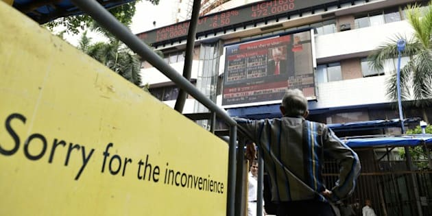 MUMBAI, INDIA - JUNE 25: People look at a screen across a road displaying the Sensex on the facade of the Bombay Stock Exchange building after Britain's exit from the European Union (EU), on June 25, 2016 in Mumbai, India. Britain voted to break away from the European Union on Friday, shattering the unity of a 60-year-old continental bloc, prompting the exit of Prime Minister David Cameron and rattling the world of finance and business. In India, shares fell more than 4% on the news but recovered by half after authorities moved to calm investor worries. The benchmark BSE ended 2.2% down, its biggest single-day percentage fall since February. (Photo by Arijit Sen/Hindustan Times via Getty Images)