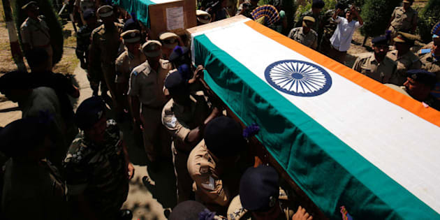 SRINAGAR, INDIA - JUNE 26: Senior police and paramilitary officers carry the coffins containing the bodies of slain Central Reserve Police Force (CRPF) men who had lost their lives in an encounter with Lashkar terrorists in Pampore during a wreath laying ceremony on the outskirts of Srinagar, on June 26, 2016 in Srinagar India. Eight Central Reserve Police Force men were killed and 20 others were injured after militants ambushed a convoy of the security force on the Srinagar-Jammu national highway in Jammu and Kashmir's Pulwama district. Two militants were also killed in the gunfight, the second major attack on a security convoy this month. (Photo by Waseem Andrabi/Hindustan Times via Getty Images)