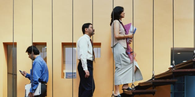 Business colleagues walking up stairs in office
