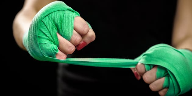 Woman is wrapping hands with green boxing wraps. Isolated on black with red nails. Strong hand and fist, ready for fight and active exercise. Women self defense.