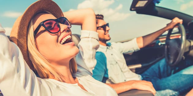 Side view of joyful young woman relaxing on the front seat while her boyfriend sitting near and driving their convertible