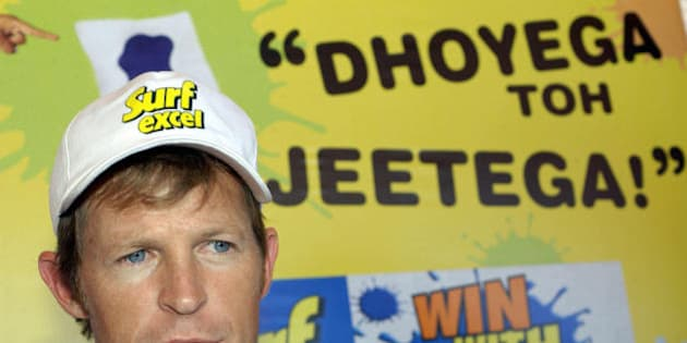 BANGALORE, INDIA:  Former South African cricketer Johnty Rhodes speaks to mediapersons after washing a  huge stained cloth alongwith destitute slum children during a promotional campaign titled Surf Excel 'Win With Stains' of an Indian detergent powder in Bangalore 04 December 2004. Rhodes, is in India as part of a countrywide promotional campaign for the detergent company Hindustan Lever Limited(HLL).  HLL is offering its consumers to win various prizes ranging from a dictionary to a personal computer or an INR 500,000(USD 0.5 million) scolarship by washing a stained piece of cloth. The writing in the background implies ' If you wash stains , you will win'.  AFP PHOTO/Indranil MUKHERJEE  (Photo credit should read INDRANIL MUKHERJEE/AFP/Getty Images)