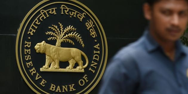 A pedestrian walks past India's central bank - Reserve Bank of India (RBI) logo in Mumbai on June 7, 2016.
