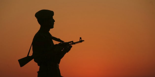 An Indian policeman is silhouetted against the setting sun as he stands guard on the banks of river Tawi ahead of India's Republic Day celebrations in Jammu January 23, 2012. India will celebrate its Republic Day on Thursday. REUTERS/Mukesh Gupta (INDIAN ADMINISTERED KASHMIR - Tags: MILITARY TPX IMAGES OF THE DAY)
