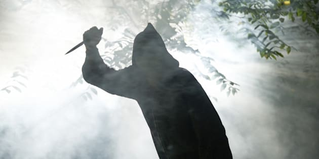 hooded monster with knife in forest coming towards camera light and fog around