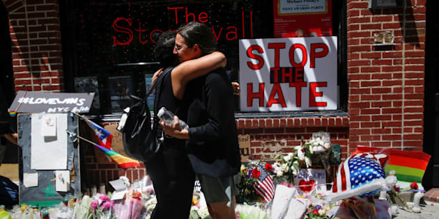 Matti Mejia (L) and Shaina Roberts embrace after laying flowers at a memorial outside The Stonewall Inn remembering the victims of the Orlando massacre in New York, U.S., June 13, 2016.  REUTERS/Shannon Stapleton
