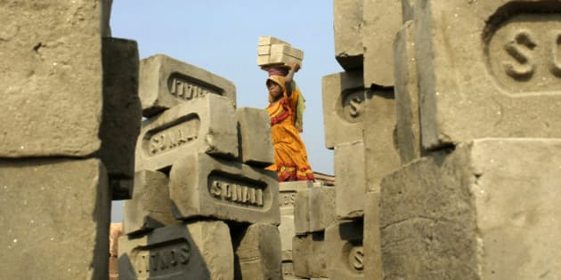 A child labourer carries bricks inside a brick factory on the outskirts of the eastern Indian city of Kolkata December 26, 2006. REUTERS/Krishnendu Halder (INDIA)