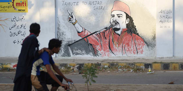 Pakistani cyclists ride past a wall image of late Sufi musician Amjad Sabri alongside a street in Karachi on June 27, 2016.