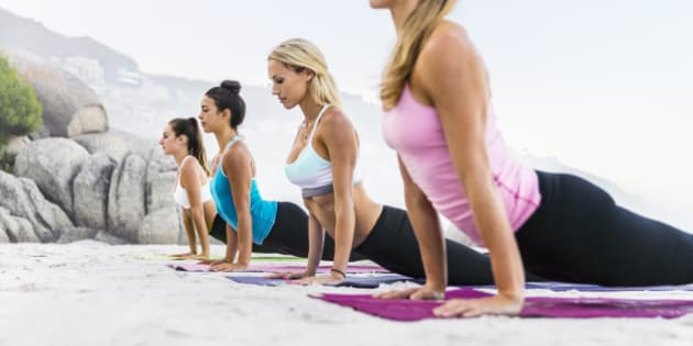 Women focusing on healthy exercise by the sea on a sandy beach while doing physical, mental, and spiritual practicesdisciplines which aim at transforming body and mind.