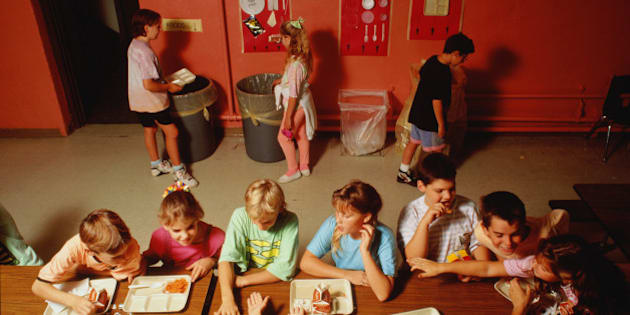 School children recycling eating utensils in refectory