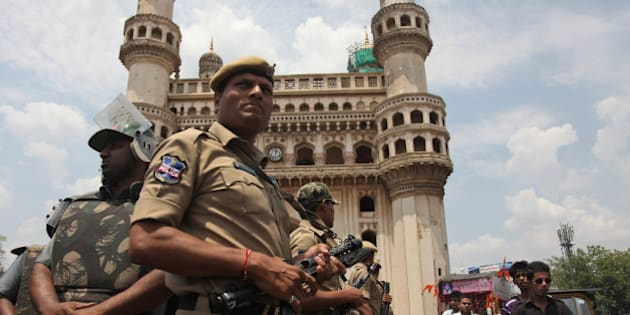 Indian policemen stand guard in front of the landmark Charminar during Friday prayers at Mecca Masjid in Hyderabad, India, Friday, April 10, 2015. Security was increased as a preventive measure on the first Friday following the killing of five prisoners, including one accused of terrorism, when, according to the police, they tried to escape from a police van on Tuesday. (AP Photo/Mahesh Kumar A.)