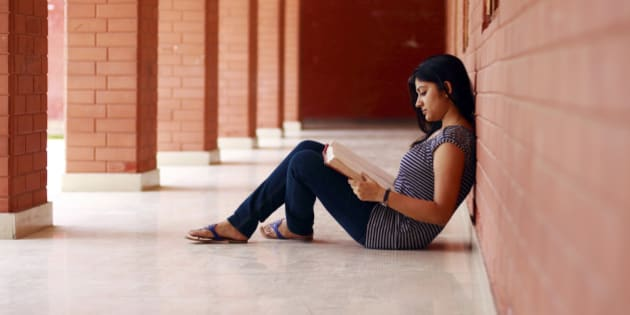 An Indian student reading a book.