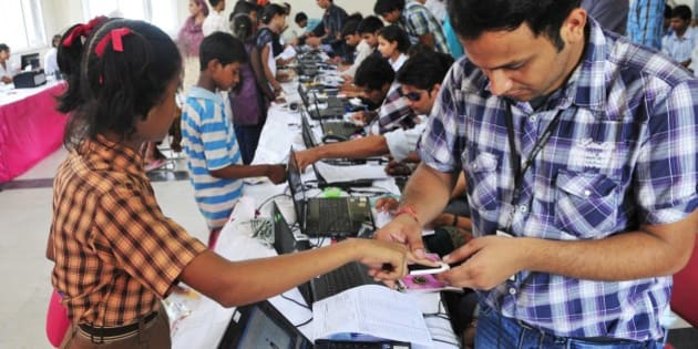 NEW DELHI, INDIA - JULY 24: People stand in queue during Aadhar card camp, pilot project for authentication of UID cards at Mayur Vihar, Phase 2, on July 24, 2012 in New Delhi, India. (Photo by Ramesh Pathania/Mint via Getty Images)