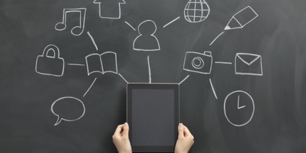 Hand holding a tablet, a symbol associated with it drawn on a blackboard