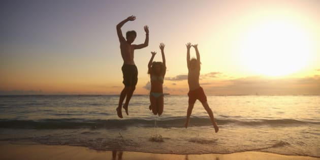 Caucasian children jumping for joy on beach