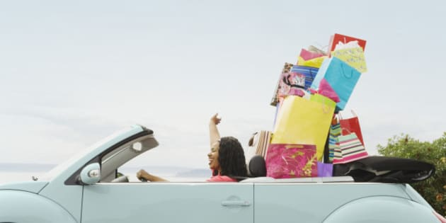 African woman in convertible with shopping bags