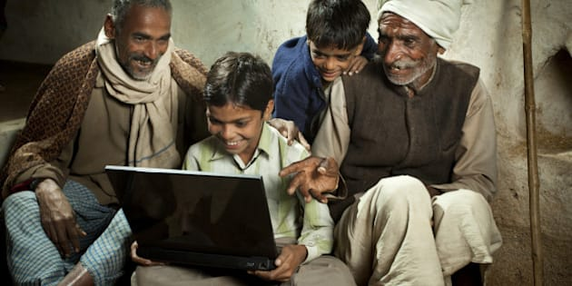 Happy village boy sitting cross-legged and using a laptop in the company of his father, grandfather and younger brother. This rural scene in India is taken beside an adobe wall with the grandfather's bamboo walking stick leaning against it in the background. The grandfather is pointing at the laptop and questioning his grandson, the father is looking with fascination at what his son is doing with the laptop and the boy's younger brother is peeking out from behind to see what is happening. This group portrait is shot at night with studio lights.