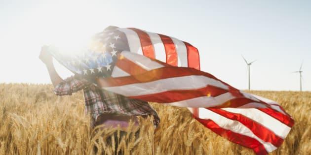 USA, Oregon, Wasco, Girl (12-13) flying american flag in wheat field