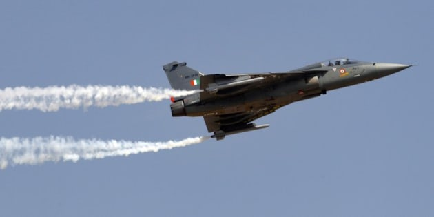 Tejas, an Indian Air Force light combat aircraft, leaves a trail of smoke as it flies on the final day of Aero India air show at Yelahanka air base in Bangalore, India, Sunday, Feb. 22, 2015. Aero India is a biennial event with flying demonstrations by stunt teams and militaries and commercial pavilions where aviation companies display their products and technology. (AP Photo/Aijaz Rahi)