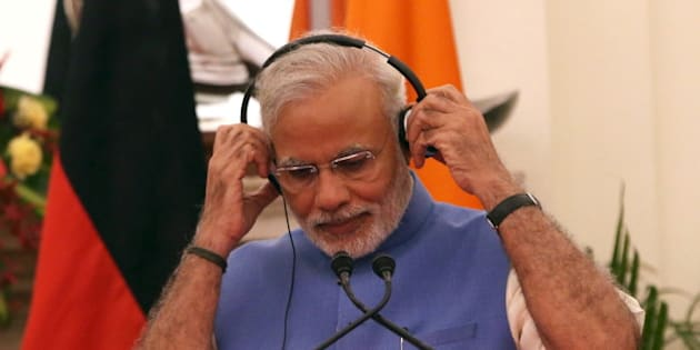 India's Prime Minister Narendra Modi adjusts his headphones during a joint statement with German Chancellor Angela Merkel (not pictured) after their delegation level talks at Hyderabad House in New Delhi, India, October 5, 2015. Merkel is on a three-day state visit to India. REUTERS/Adnan Abidi