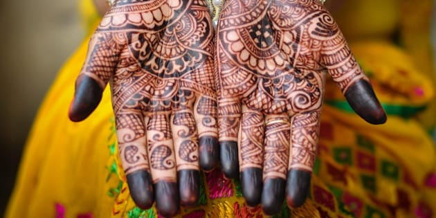 An Indain bride's hand with henna tattoos. An Indian bride showing her palms painted with a traditional mehandi design. The mehandi design is in sharp focus and no human face visible in the photograph.