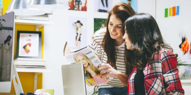 Two female fashion bloggers watching magazine at office