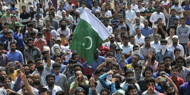 SRINAGAR, INDIA - JUNE 15: People shout anti-national slogans and raise flag of Pakistan during funeral of slain militant Tanveer Sultan, who was killed in a firing incident in Kud town of Udhampur district at Bemina on June 15, 2016 in Srinagar, India. The family claims he was a psychiatric patient and was travelling to Amritsar for treatment. The Jammu and Kashmir government confirmed that the person killed in a firing incident in Kud town of Udhampur district was a militant who had fired at the security forces. (Photo by Waseem Andrabi/Hindustan Times via Getty Images)