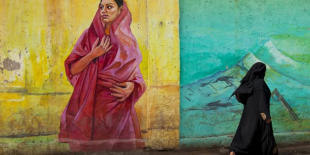 Local muslim woman dressed in a in black burqa is walking pass a wall painting in the city of Bangalore, India. The wall painting is in primary colors and shows a local woman in a red sari dress.