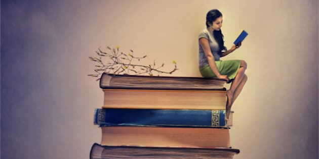 A girl sitting on a pile of book and also reading one. Miniature image.