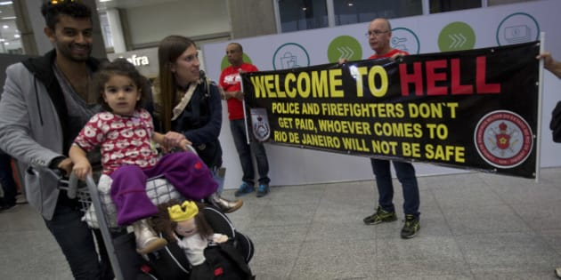 """A family arrive to Brazil, while they walk past a banner that reads """"Welcome to hell"""" during a police protest, demanding their payments and better labor conditions, at the Tom Jobim International Airport, in Rio de Janeiro, Brazil, Monday, July 4, 2016. Brazil is suffering the worst recession in decades and Rio's acting governor has declared a state of financial disaster this month, largely to bolster spending on security as the world's spotlight turns to the city. (AP Photo/Silvia Izquierdo)"""