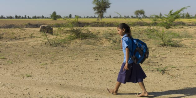 INDIA - MARCH 15:  Young Indian girl in school uniform walking barefoot to her school near Rohet in Rajasthan, Northern India  (Photo by Tim Graham/Getty Images)